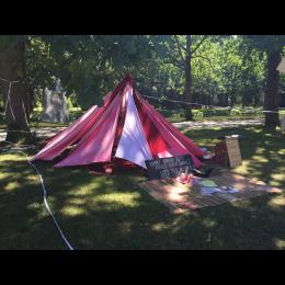 Bild zeigt eine Art Zelt aus einzelnen Stoffbahnen in Rottönen.  Das Zelt steht im Grünen. Vor dem Zelt liegt ein Teppich. Daneben lehnt ein hölzernes Schild.