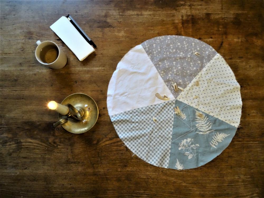 Auf hölzernem Grund eine Kerze, eine Tasse Tee, ein Stapel Zettel, ein Stift und eine Runde Decke aus fünferlei Tuch in weiß, mint und grautönen. Sie ist mit einer fünfeckigen Stickerei versehen. Auf er Decke liegen zehn Zähne eines Frischlings.