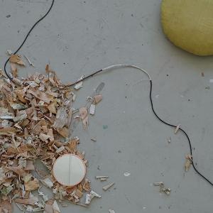 Vogelperspektive. Auf dem grauen Boden liegen ein runder Spiegel mit Kupferfarbenem Rand, ein rundes gelbes Seidenkissen, zwei Kabel, davon eines an einen Stock angeschlossen und ein Haufen Birkenrinde. Bild verlinkt zu Arbeit 2.
