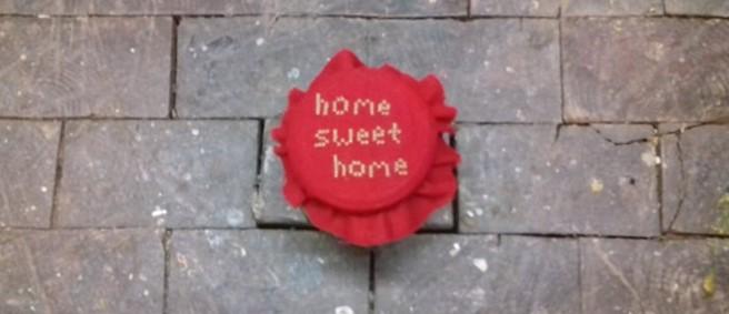 """Ein Schraubglas mit rotem Stoffdecken darauf. Es ist im Keuzstich mit dem Schriftzug """"home sweet home"""" bestickt. Es steht auf einem Boden aus Holzklötzern."""