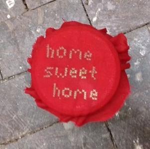 """Ein Schraubglas mit rotem Stoffdecken darauf. Es ist im Keuzstich mit dem Schriftzug """"home sweet home"""" bestickt."""