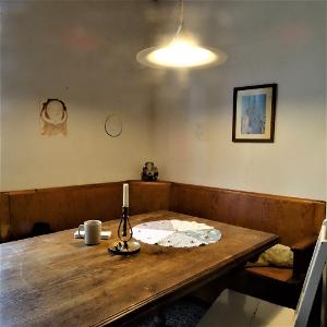 Link zur Arbeit IHolle. Eine hölzerne Sitzecke. An der linken Wand zwei Zeichnungen. An der rechten Wand eine Zeichnung und ein gerahmtes Foto. Vor der Sitzecke ein Tisch. Darauf befinden sich eine Kerze, eine Tasse Tee, ein Stapel Zettel, ein Stift und reine runde Decke aus fünferlei Stoff mit zehn Zähnen darauf.