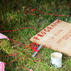 Das Bild zeigt ein Stück Wiese. Darauf liegen rote Schnüre, Zeltheringe undein Brett mit der Aifschrift Programm. Das Bild verlinkt zur Arbeit Rotes Zelt