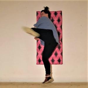 Bild verlinkt zur Arbeit WTFX.Performances. Tristan Marie springt gegen ein gepolstertes Brett an der Wand. Das Polsterbrett ist Pink und Auberginefarben gemustert.