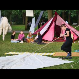 Bild zeigt eine Art Zelt aus einzelnen Stoffbahnen in Rottönen.  Das Zelt steht im Grünen. Vor dem Zelt liegt ein Teppich auf dem menschen in ein Gespräch vertieft sitzen.
