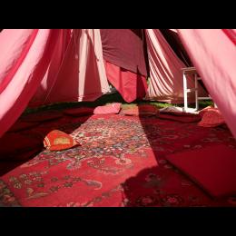 Das Bild zeigt einen roten Musterteppich, und rote Kissen unter Zeltwänden aus einzelnen roten Stoffbahnen.